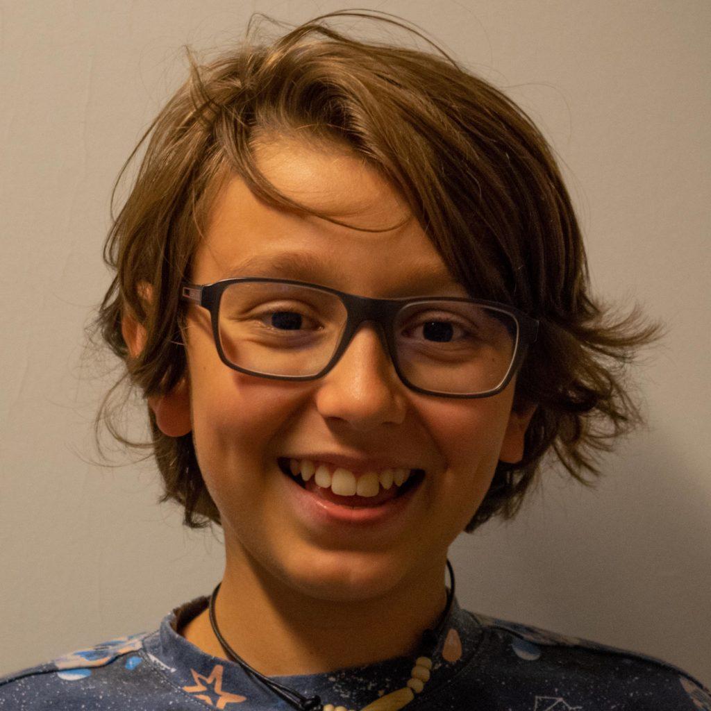 ein Bub mit längeren braunen Haaren und Brille lacht